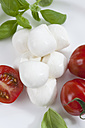 Mozzarella cheese balls, tomatoes and basil herb on plate, close up - CSF018524