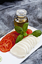 Slices of mozzarella cheese, tomatoes and basil herb on chopping board, close up - CSF018527