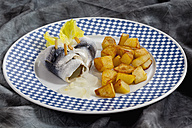 Rollmop herring with roasted potatoes and onions on a plate - CSF018789