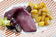 Sherry herring with roasted potatoes, onion and grapes on plate - CSF018795