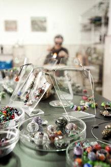 Germany, Bavaria, Mature woman making glass beads - RNF001197