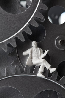 Figurine sitting on gear wheels, close up - CSF018823