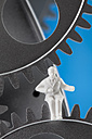Figurine sitting on gear wheels, close up - CSF018821