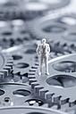 Figurine of businessman standing on gear wheels, close up - CSF018818