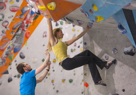 Germany, Bavaria, Munich, Young man helping woman to climb - HSIYF000218