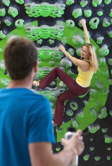 Germany, Bavaria, Munich, Young man looking at woman while bouldering, smiling - HSIYF000198