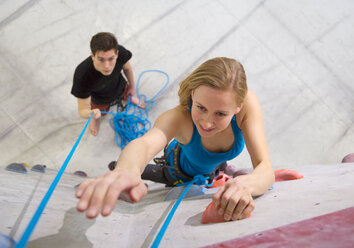Germany, Bavaria, Munich, Young woman bouldering while man holding rope - HSIYF000233