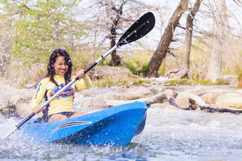 USA, Texas, Young woman kayaking on Frio River, smiling - ABAF000807
