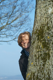 Germany, Baden Wuerttemberg, Constance, Mature woman hidding behind tree, smiling - JEDF000024