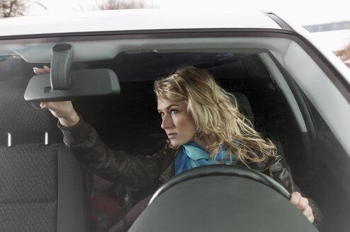 Germany, Brandenburg, Woman looking in rearview mirror - BFRF000220