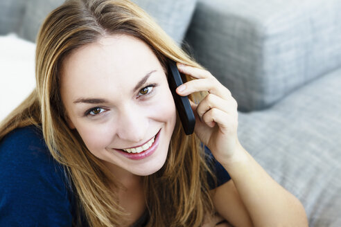 Germany, Bavaria, Munich, Portrait of young woman talking on mobile phone, close up - SPOF000295