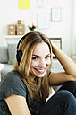 Germany, Bavaria, Munich, Portrait of young woman listening music, smiling - SPOF000312