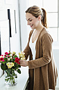 Germany, Bavaria, Munich, Young woman arranging flowers in vase, smiling - SPOF000318