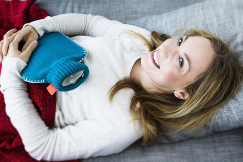Germany, Bavaria, Munich, Portrait of young woman lying on couch with hot water bottle, smiling - SPOF000328