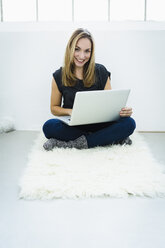 Germany, Bavaria, Munich, Portrait of young woman using laptop, smiling - SPOF000332