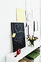 Germany, Bavaria, Munich, Text on blackboard with telephone and flower vase on shelf - SPOF000275