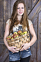 Germany, Portrait of teenage girl holding basket with organic apples, smiling - ONF000172
