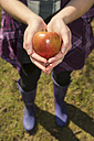 Germany, Teenage girl holding organic apple - ONF000175