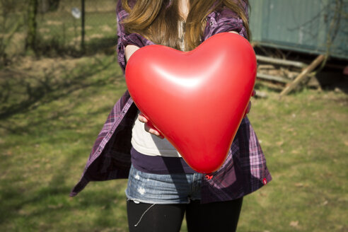 Germany, Teenage girl holding heart shaped balloon - ONF000164