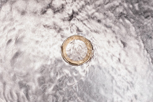 Euro coin in kitchen sink with flowing water, close up - KJF000219