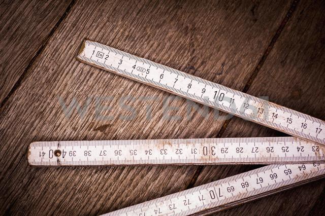 Old folding ruler on wooden background, close up - KJF000220