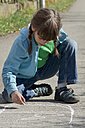 Germany, Tuebingen, Girl drawing hopscotch on street with chalk - LV000028