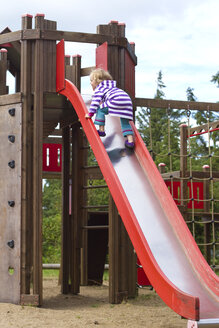 Germany, Girl climbing on slide - JFEF000083