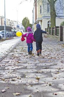 Germany, Kiel, Boy and girl walking on street - JFEF000089