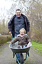 Germany, Father pushing daughter on wheel barrow, smiling - JFEF000085
