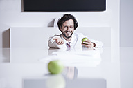 Germany, North Rhine Westphalia, Cologne, Portrait of businessman holding green apple, smiling - FMKF000751