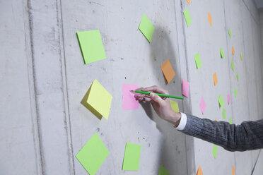 Germany, North Rhine Westphalia, Cologne, Businesswoman writing on adhesive note - FMKF000785