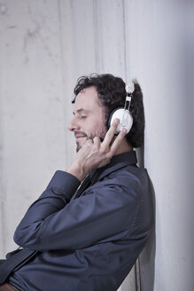 Germany, North Rhine Westphalia, Cologne, Businessman listening music with headphones - FMKF000799