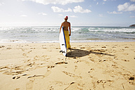 USA, Hawaii, Mid adult woman standing with surfboard on beach - SKF001279