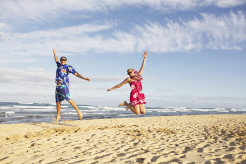 USA, Hawaii, Mid adult couple jumping on beach - SKF001293