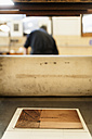 Germany, Bavaria, Copperplate in print shop while man standing in background - TC003441