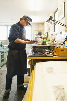 Germany, Bavaria, Mature man looking at copperplate in print shop - TC003437