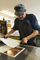 Germany, Bavaria, Mature man holding deckle edge paper above copperplate in print shop - TC003438