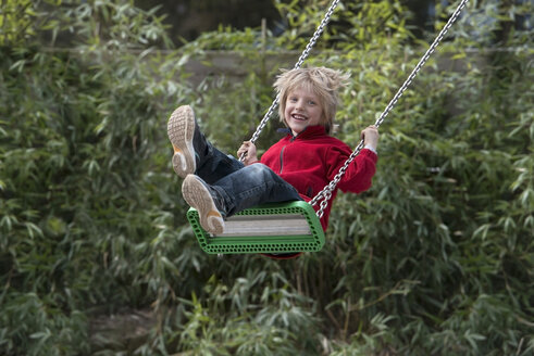 Austria, Linz, Boy swinging on swing in wild garden - CW000039