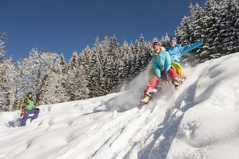 Austria, Salzburg, Young man and women with sledge in snow at Altenmarkt Zauchensee - HHF004594
