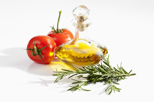 Rosemary herb with tomatoes and olive oil bottle on white background, close up - CSF019076