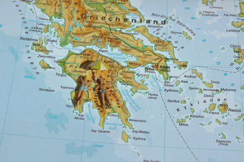 Greece, Couple of figurines laying on map - AX000449