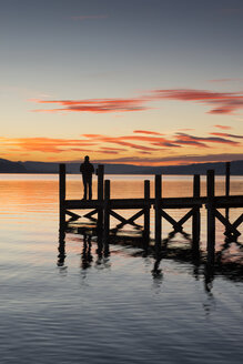 Germany, Baden Wuerttemberg, Person standing on pier at Lake Constance at dusk - EL000010