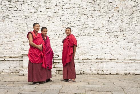 Bhutan, Three monks in Trongsa dzong courtyard - HL000173