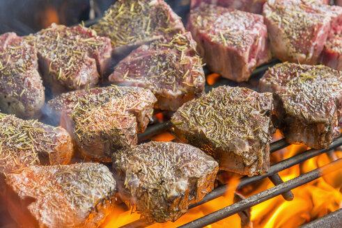 Grilling T bone steaks on barbecue, close up - ABAF000836