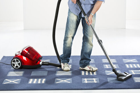 Mature man cleaning carpet with vaccuum cleaner - MAEF006518