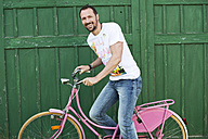 Germany, Bavaria, Portrait of mature man sitting on pink bicycle, smiling - MAEF006530
