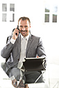 Germany, Portrait of businessman talking on mobile phone, smiling - MAEF006634