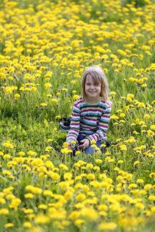 Germany, Baden Wuerttemberg, Girl sitting in meadow - SLF000086