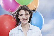 Germany, Cologne, Young woman  with balloons, close up - FMKF000825