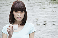 Germany, Cologne, Portrait of young woman holding coffee cup - FMKF000850